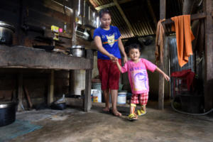 Selma with her mum in the kitchen. With the aid of her leg splints (funded by LF) Selma is now able to walk.