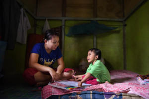Selma and her mum Acu in the bedroom. Here Selma likes to write and play, as the mattras is soft she can also practice standing up. Acu is a caring mother who tries to make Selma as independent as possible by teachging her all she knows.