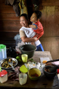 Moses and his mum in the kitchen, just home after school. She carries him inside from the motorbike so he can be in the kitchen amongst family.